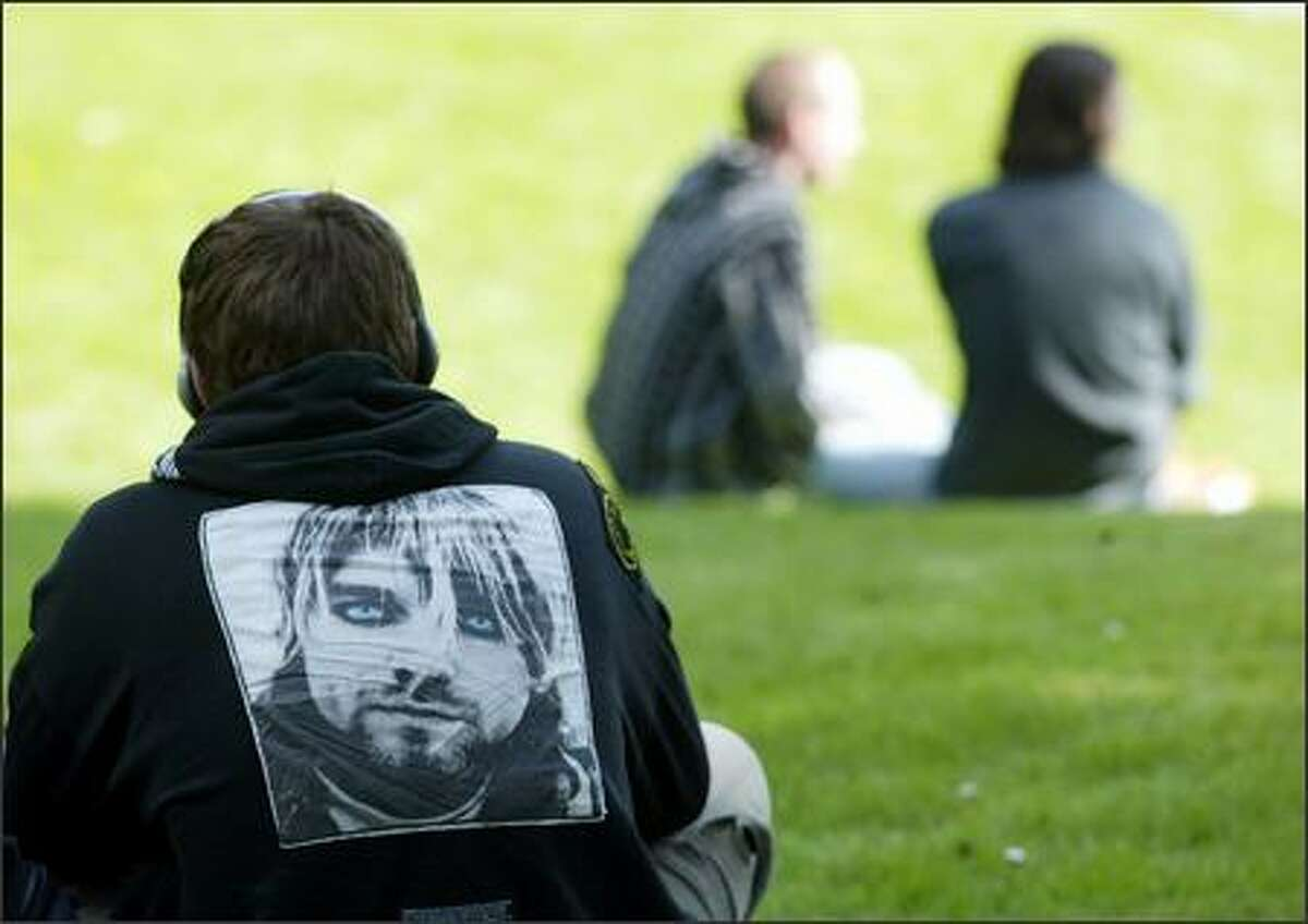 Justin Sevier wears a jacket with the image of Kurt Cobain on the back as helistens to a Nirvana tune through headphones at Viretta Park in Seattle.