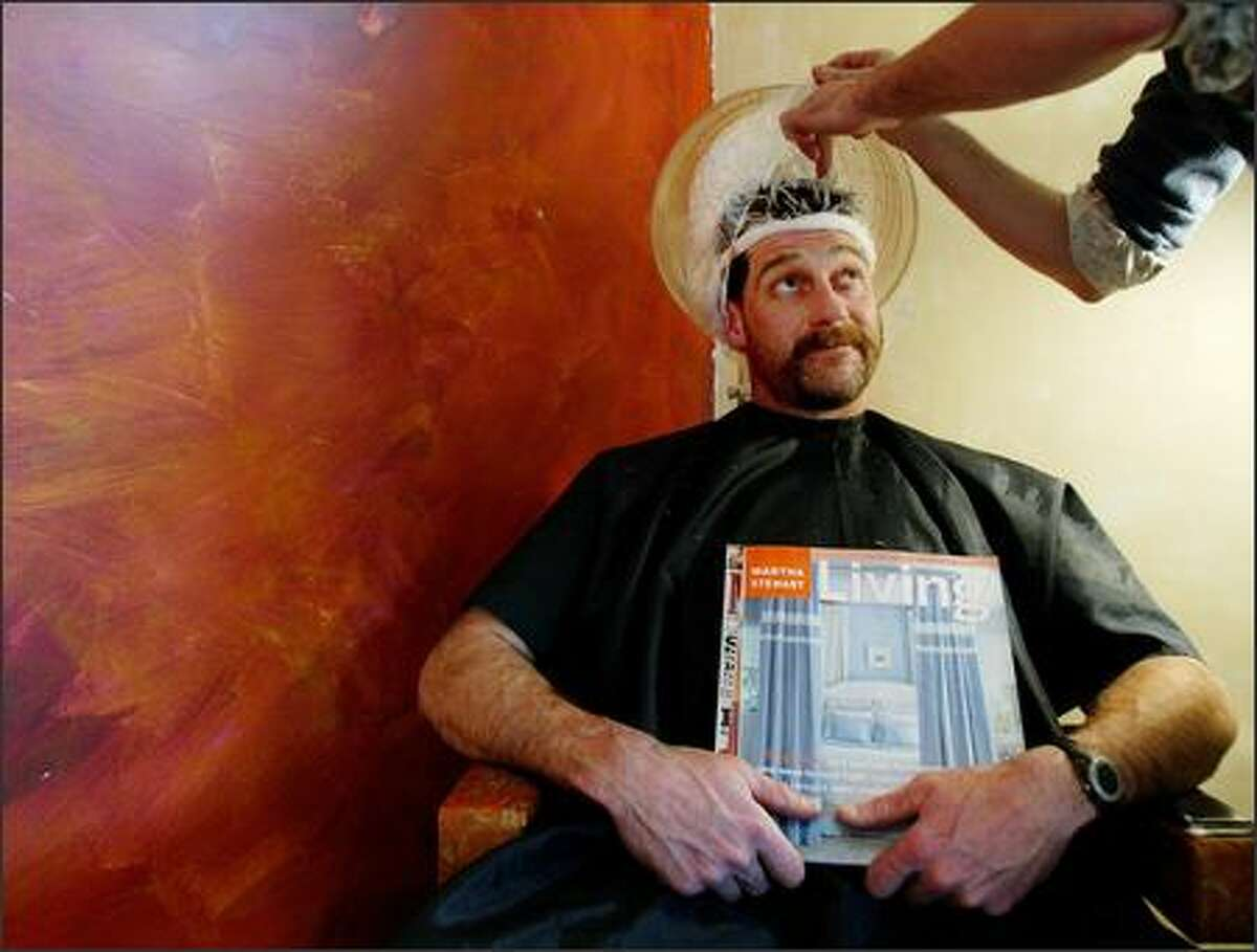 Stylist Patrick Bertels at work on the very thick hair of Bellingham contractor John Harris. Harris was chosen to be the makeover subject of five Bellingham-area gay men as part of a Queer Plan for the Straight Man benefit.