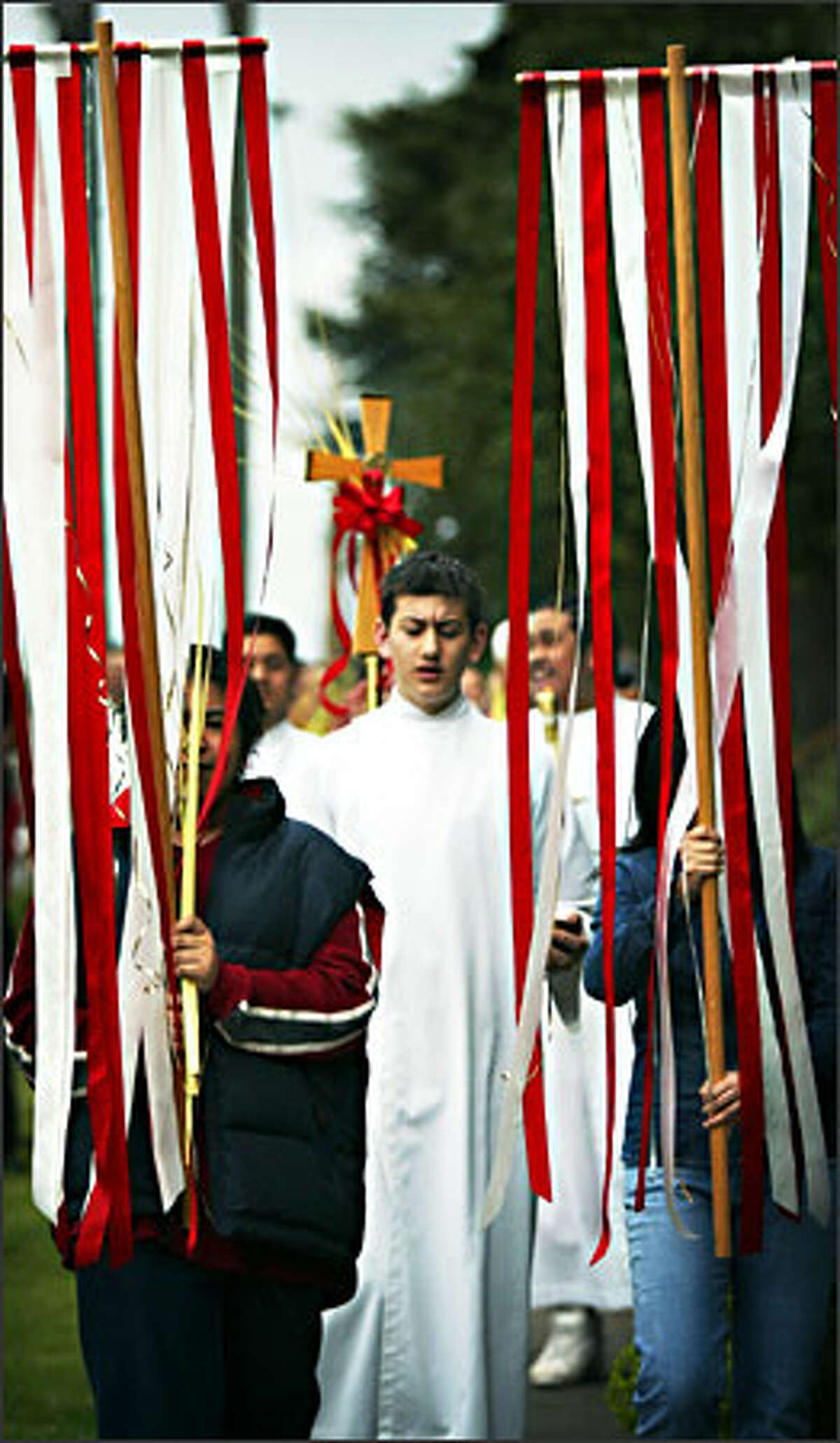 A parishoner holds a cross made from a palm frond during a Palm Sunday procession at St. George Parish in south Seattle on Sunday. Parishoners walked from St. George's School to the church down the block, carrying palm fronds and singing in celebration of Palm Sunday. Palm Sunday is celebrated as the day that Jesus entered Jerusalem and begins a holy week that ends with Easter Sunday.