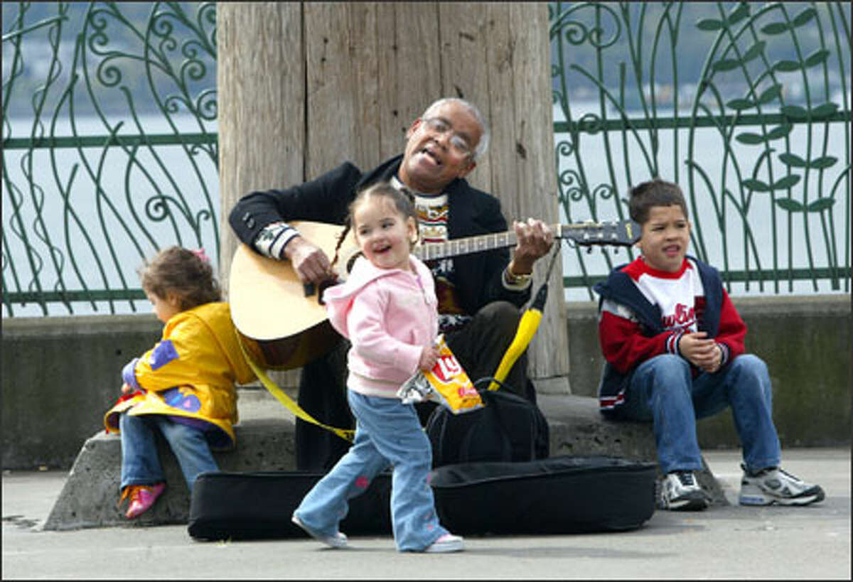 Street musician Norm Lawrence entertains little tourists visiting Victor Steinbrueck Park in Seattle with