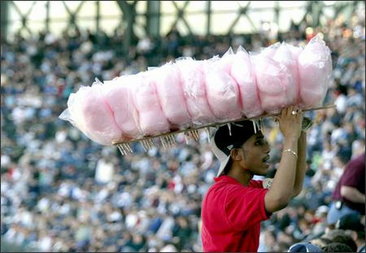 Vendor Charles Sparks works the stands with a load of cotton candy. He had a full house at Safeco Field yesterday to buy his goods. And that included plenty of prime customers -- young fans -- among them.