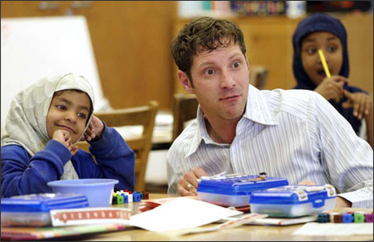Rainier View Elementary first-grade teacher Dan Jordan works with Munira Abdirahman, left, and other students on math skills.