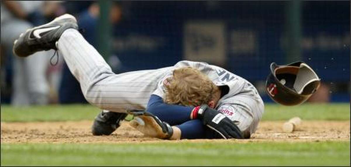 Minnesota's Justin Morneau hits the dirt after being struck in the head by Mariners reliever Ron Villone in the eighth inning.