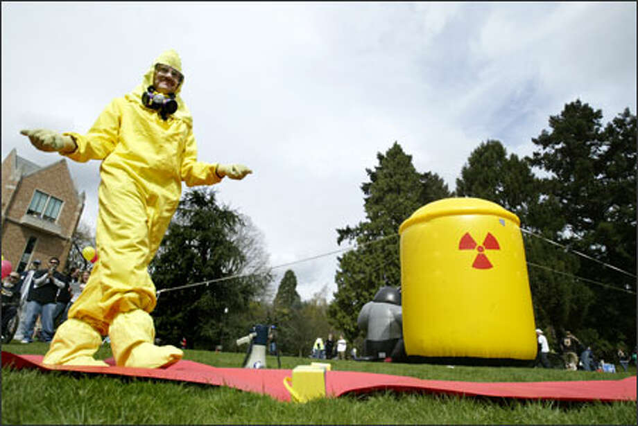 "Jay Herzmark of the Washington Federation of State Employees walks the ""red carpet"" during the Hazmat Suit Fashion Show at the University of Washington campus Thursday. The Student Labor Action Project held the event to call attention to the UW's decision to use LVI Environmental Services to remove hazardous materials from the university's nuclear reactor building. Photo: Dan DeLong, Seattle Post-Intelligencer / Seattle Post-Intelligencer"