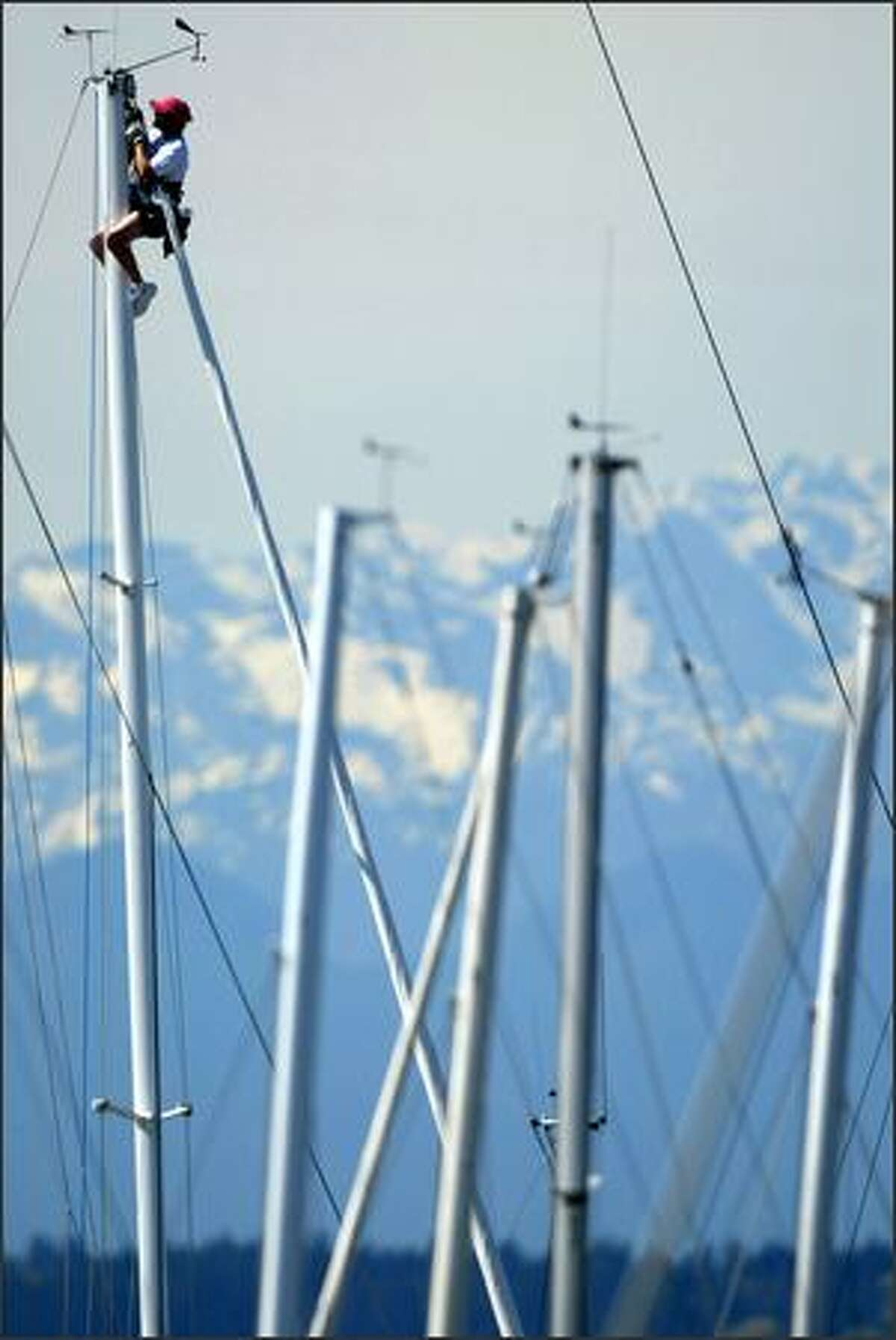 Dave White takes advantage of warm weather Friday while he works on the rigging of the sailboat Kaulana at Shilshole Bay Marina in Ballard. The Olympic Mountians are seen in the background. Photo by Joshua Trujillo / Seattle Post-Intelligencer