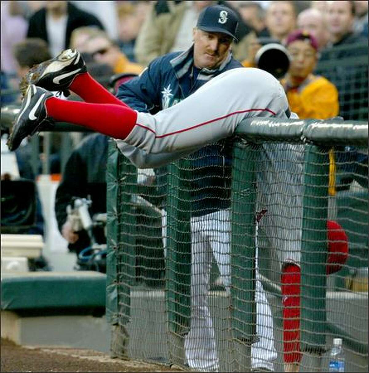 Angels first baseman Darin Erstad hangs over the railing protecting the Mariners dugout as he fails to catch a Bret Boone foul popup.