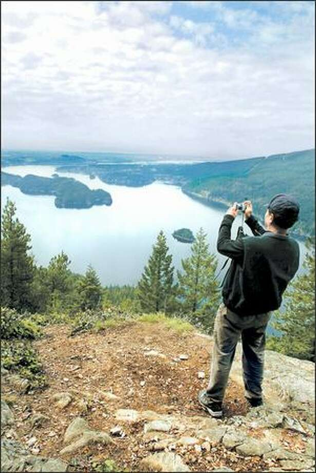 Yang Cheng of Coquitlam, B.C., frames his shot of Indian Arm, an extension of Burrard Inlet, from the Diez Vistas Trail in the Buntzen Lake Reservoir Recreation Area near Port Moody. Photo: Paul Joseph Brown, Seattle Post-Intelligencer / Seattle Post-Intelligencer