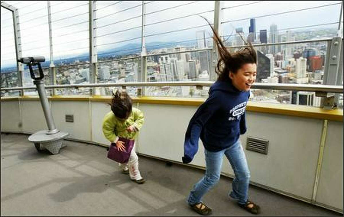 Alyssa Fruge-Culanag, 9, and her younger sister Remy, 5, try to stay upright while pushing through a stiff wind while walking laps around the top of Seattle's Space Needle on Monday. High winds blew around the region during the morning and into the afternoon.