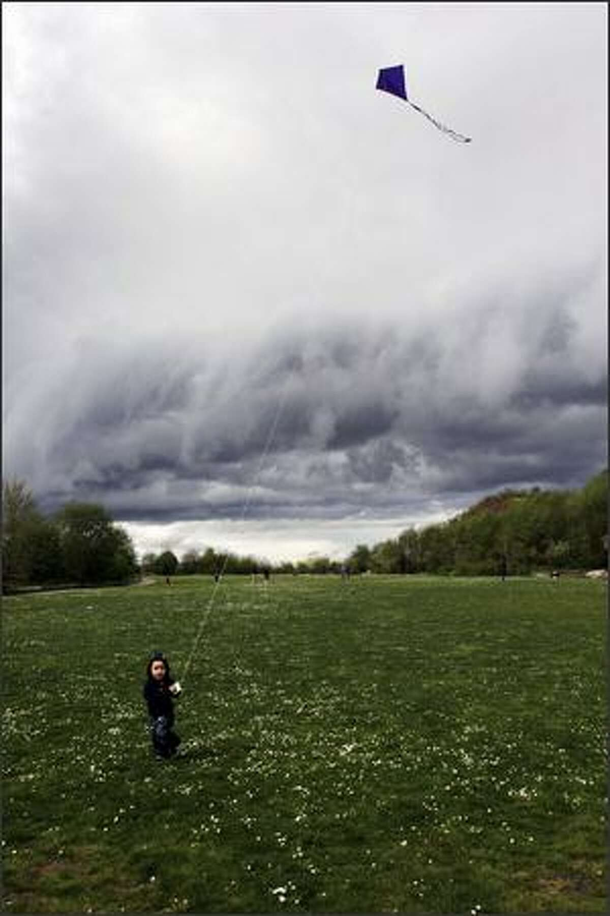 Rocco Marckx, 2, of Seattle didn't care about the roiling clouds behind him while flying his kite at Golden Gardens Park.