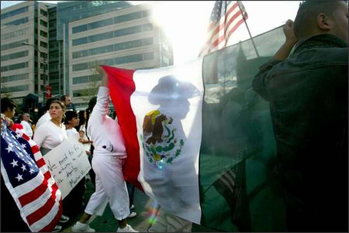 Thousands flooded Seattle streets during a large immigrant-rights march on Monday. Here, demonstrators move along King Street in the International District bearing a large Mexican flag amid U.S. flags.