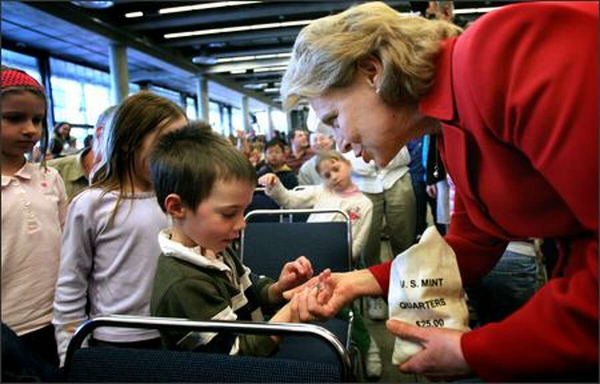 Gov. Chris Gregoire hands Peterjohn Colino, 4, a newly minted Washington quarter Wednesday after the ceremonial introduction of the new coin at the Seattle Center. Children 18 and younger received a quarter courtesy of Bank of America. Washington's quarter is the 42nd state quarter produced by the U.S. Mint. It features a leaping salmon and Mount Rainier.
