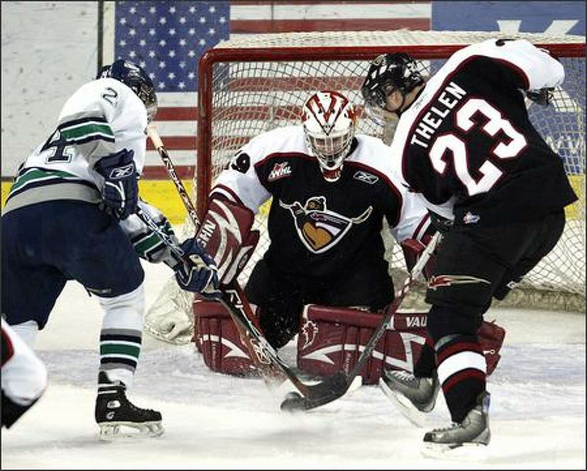 Seattle Thunderbirds' Jeremy Schappert (2) vies for the puck with Vancouver Giants' A.J. Thelen (23) as Vancouver goalie Tyson Sexsmith (29) guards the net during first period.