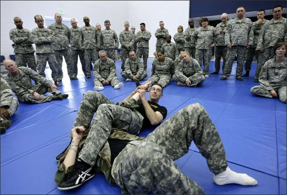 Sgt. First Class Bryan Pulak, with the 191st Infantry Brigade out of Fort Lewis, demonstrates a move to break his opponent's arm to a group of soldiers with the 70th Regional Readiness Command at Fort Lawton.