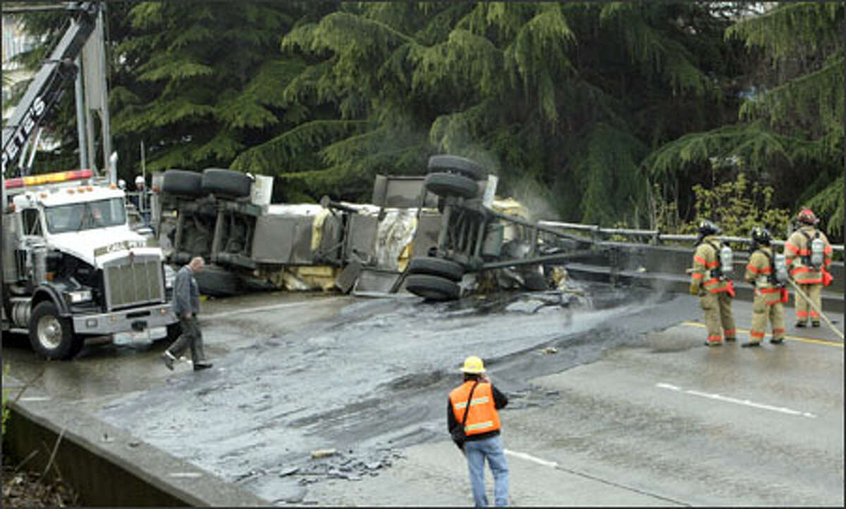 Firefighters stand by as a tow-truck driver inspects hardened roofing tar that spilled onto northbound Interstate 5 in Seattle after a tanker lost its trailer. The freeway was closed to traffic for about four hours.