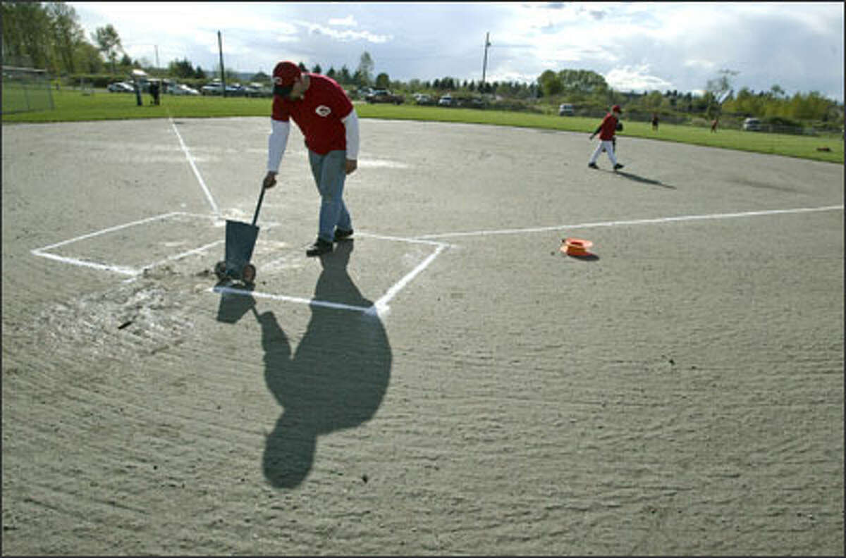 Kurt Lanter, a manager in the North Snohomish Little League, lays down the lines for the batting box before a game yesterday at a field built illegally on farmland near Snohomish.