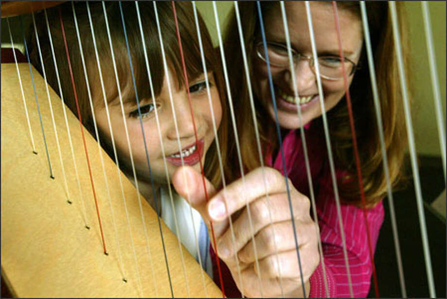 "Megan Morrell, 6, watches her instructor, harpist Juliet Stratton, demonstrate proper thumb positioning at the Washington Academy of Performing Arts in Redmond. Megan is learning to perform ""Air"" from Franz Joseph Haydn's ""Surprise"" Symphony, No. 94, in preparation for her class' May recital. Through the academy's open program, classes are available to students of almost any age. Photo: Grant M. Haller, Seattle Post-Intelligencer / Seattle Post-Intelligencer"