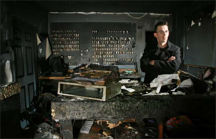 Mike Dein, owner of Puget Sound Key & Lock, stands inside what remains of his West Seattle shop. Dein, who did not have insurance, lost all his equipment when arsonists destroyed his business. Friends are holding a fundraiser to raise money for Dein on Saturday. Photo: Dan DeLong, Seattle Post-Intelligencer / Seattle Post-Intelligencer
