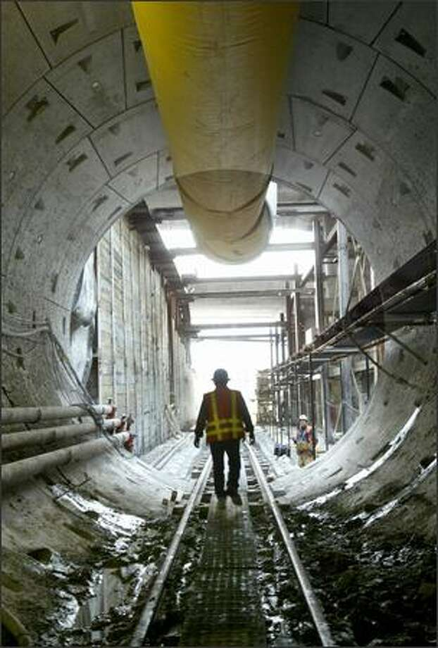 A worker leaves Sound Transit's Beacon Hill light rail tunnel during a media tour Wednesday. A 642-ton tunnel-boring machine, nicknamed the Emerald Mole, is digging the tunnel. Photo: Dan DeLong, Seattle Post-Intelligencer / Seattle Post-Intelligencer
