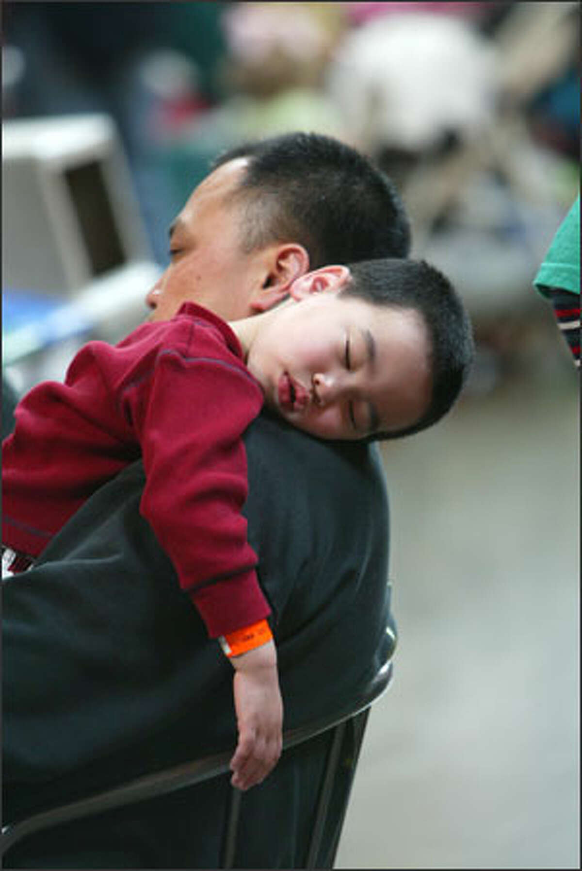 Shing Chin holds his sleeping son, Carson, 3, while watching a dance group perform at the Center House.