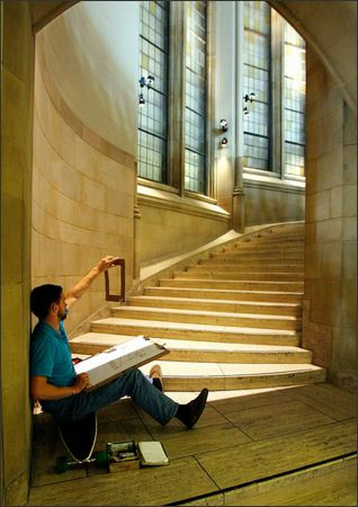 University of Washington student Max Lang holds up a cardboard viewfinder as he sketches the steps and columns of the grand staircase inside the Seattle campus's Suzzallo Library.