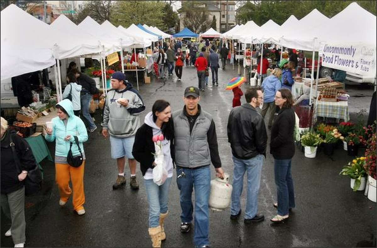 Shoppers turned out at the University District Farmers Market in Seattle despited the cold weather and rain on Saturday.