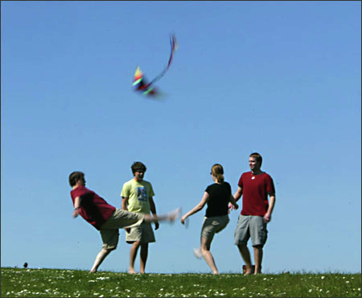 Enjoying a game of hackey sack at Magnuson Park are, from left, Chris Gragg of Redmond, Patrick Workman of Seattle, Whitney Field of Redmond and Wa Wildermuth of Seattle.