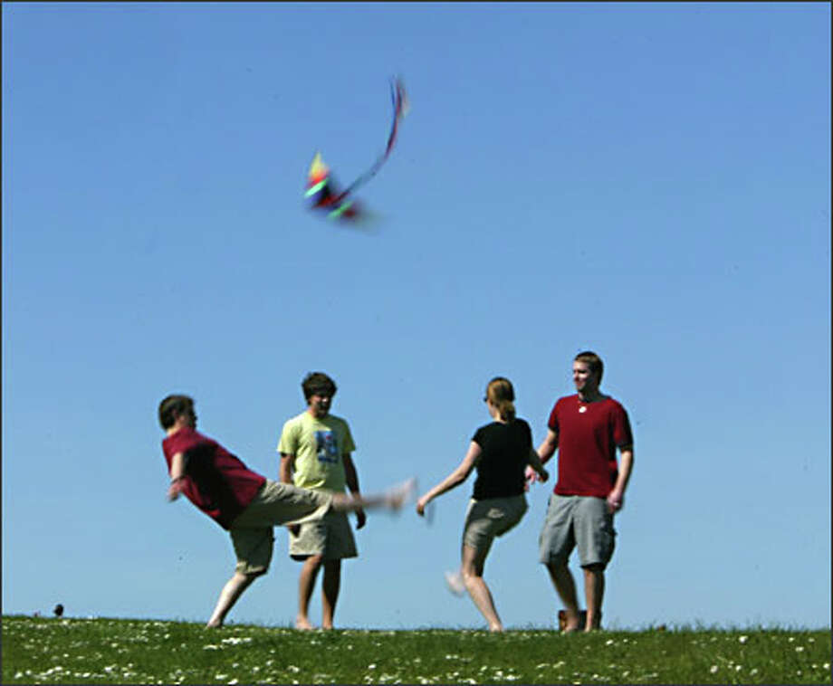 Enjoying a game of hackey sack at Magnuson Park are, from left, Chris Gragg of Redmond, Patrick Workman of Seattle, Whitney Field of Redmond and Wa Wildermuth of Seattle. Photo: Karen Ducey, Seattle Post-Intelligencer / Seattle Post-Intelligencer