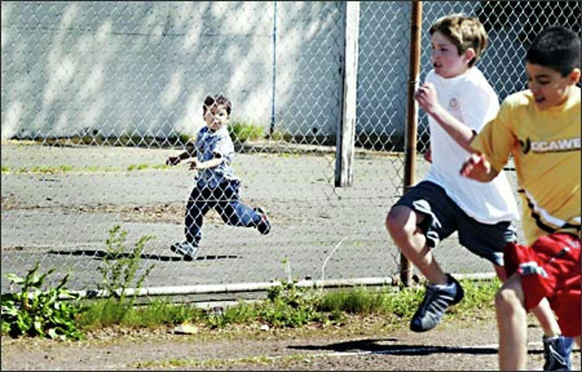 Three-year-old Liam Bracy does his best to keep up with the runners competing in the Olympiad portion of the Junior Classical League regional convention and competition in Greek and Roman classical language and culture held at Roosevelt High School Sunday.