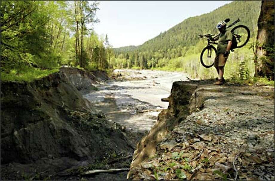 Chris Gunter of Anacortes has his biking trip along Whitechuck Road halted by a massive hole where the road was washed out during a flood in October. Photo: Joshua Trujillo, Seattlepi.com / seattlepi.com
