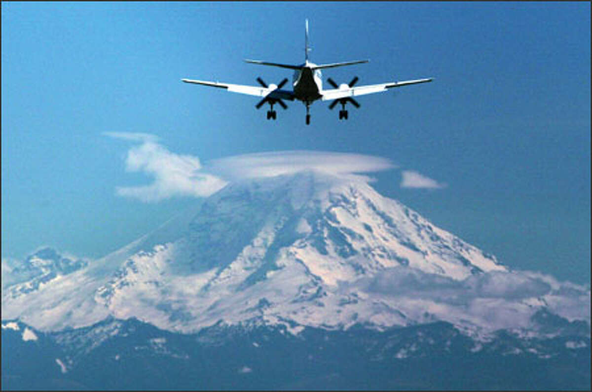 A civilian turbo prop plane heads for a landing Thursday at Boeing Field as a lenticular cloud clings to the top of Mount Rainier.