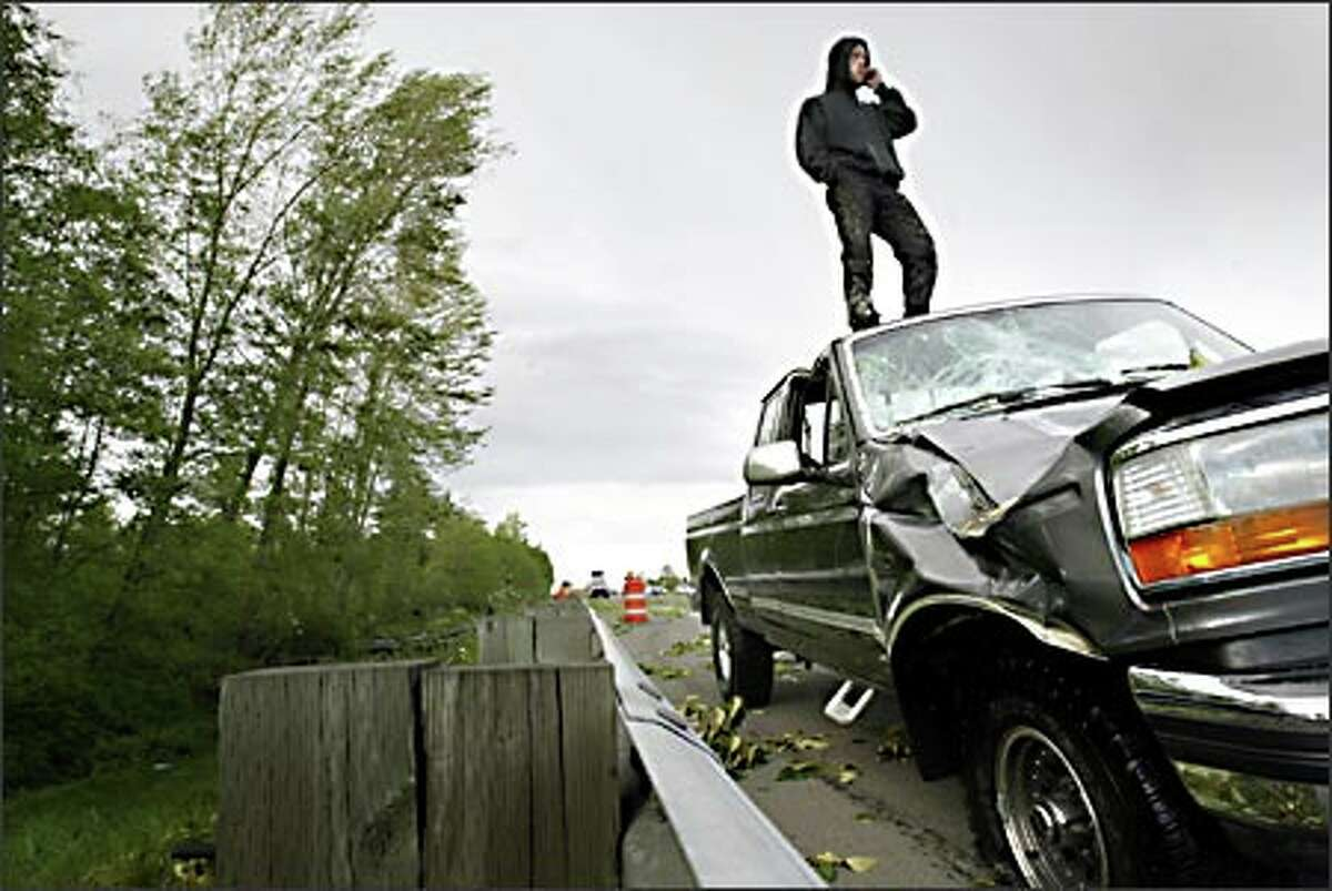 Michael Cote of Lynnwood stands atop his truck, damaged when trees fell on it along Interstate 5, near the 164th Street Southwest exit in Lynnwood. Cote was on his way home from work when the trees blew over on his truck, lifting the back end.