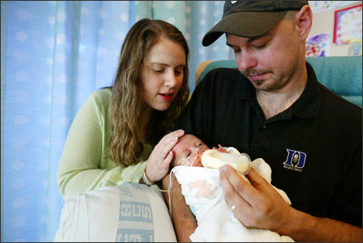 Jennifer and Chad Puetz feed 4-month-old Ethan in Swedish Medical Center's neonatal intensive care unit. Born three months early, Ethan weighed 1 pound, 11 ounces at birth.