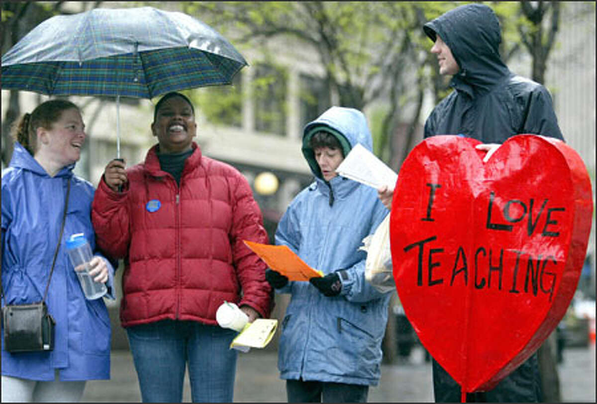 If only pennies did fall from Heaven, these preschool teachers might not have had to rally in Seattle before Worthy Wage Day, which is Sunday. Child care teachers, parents and preschoolers marched Friday from Westlake Center to Victor Steinbrueck Park. Singing in the rain, from left: Sarah Finkelstein, Deborah Mason, Penny Webb and Spencer Clauson.