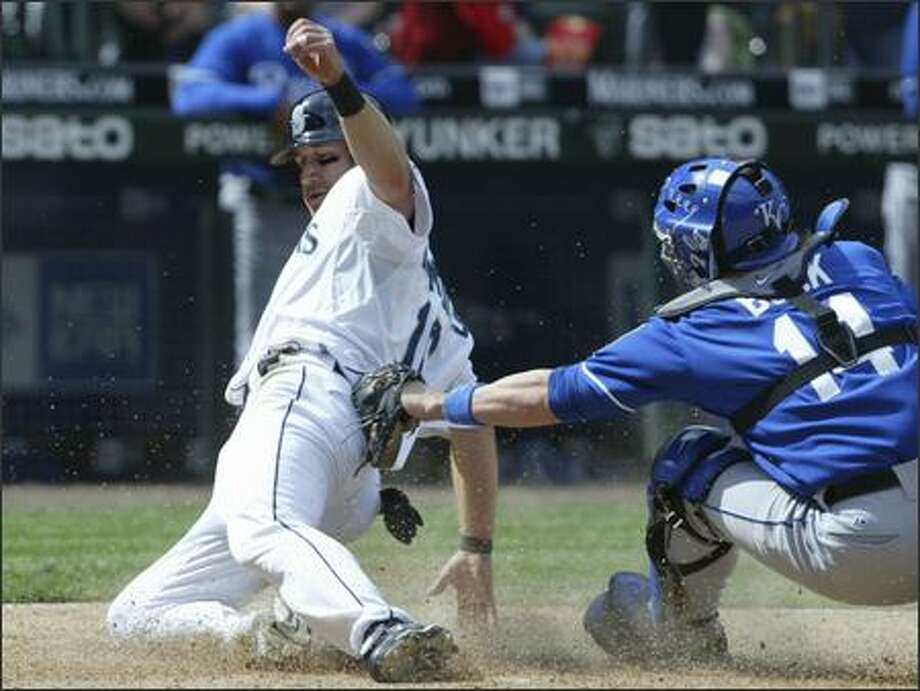 Willie Bloomquist slides home safely around the tag of Royals catcher John Buck on a single by Ichiro in the seventh inning to make the score 4-1. Photo: Andy Rogers, Seattle Post-Intelligencer / Seattle Post-Intelligencer