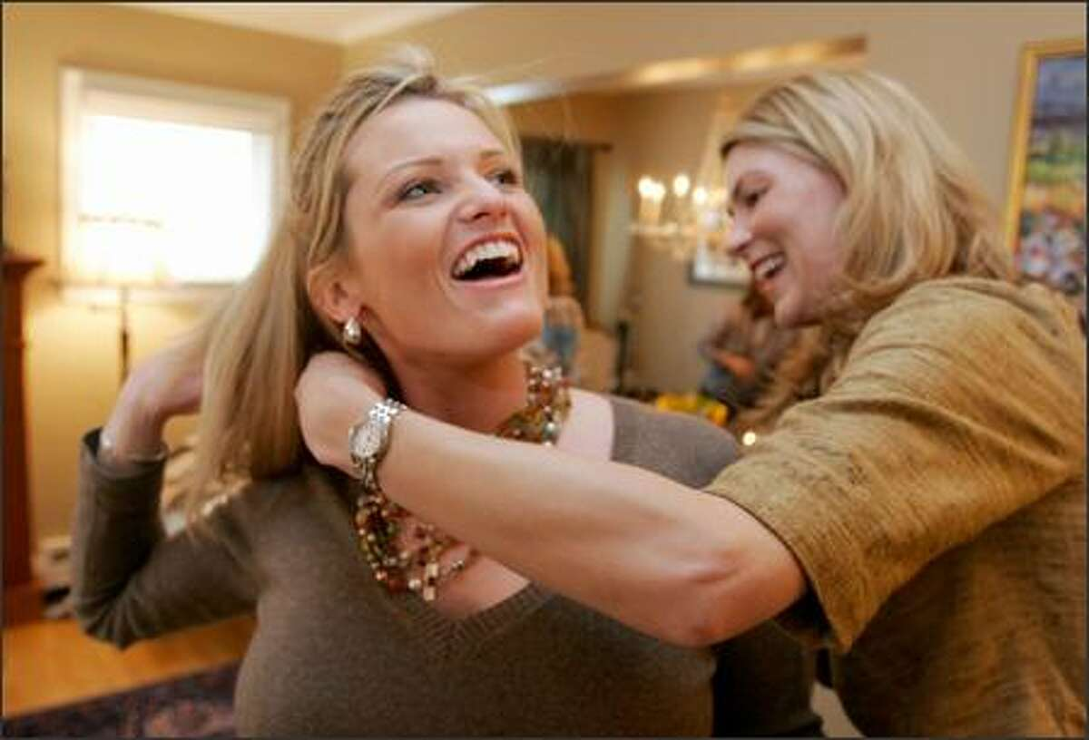 Gina Tenerelli gets help trying on a Lia Sophia necklace from Caroline Moore during a jewelry homesale by Tomika Quigg at the home of Lisa Conner.