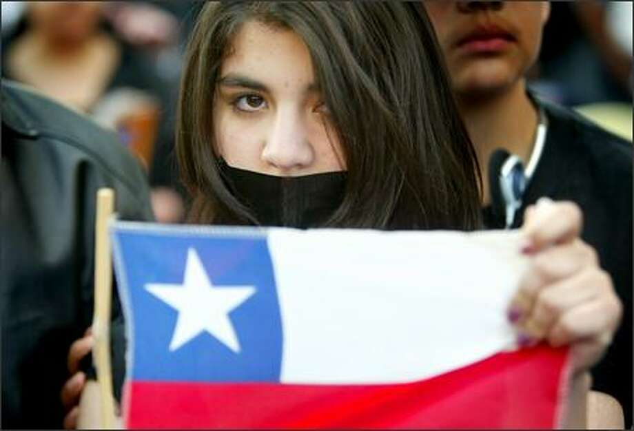 Verna Faundez, 15, from Chile, holds her country's flag during a mostly silent and solemn immigrant rights rally in downtown Seattle. Photo: Joshua Trujillo, Seattlepi.com / seattlepi.com