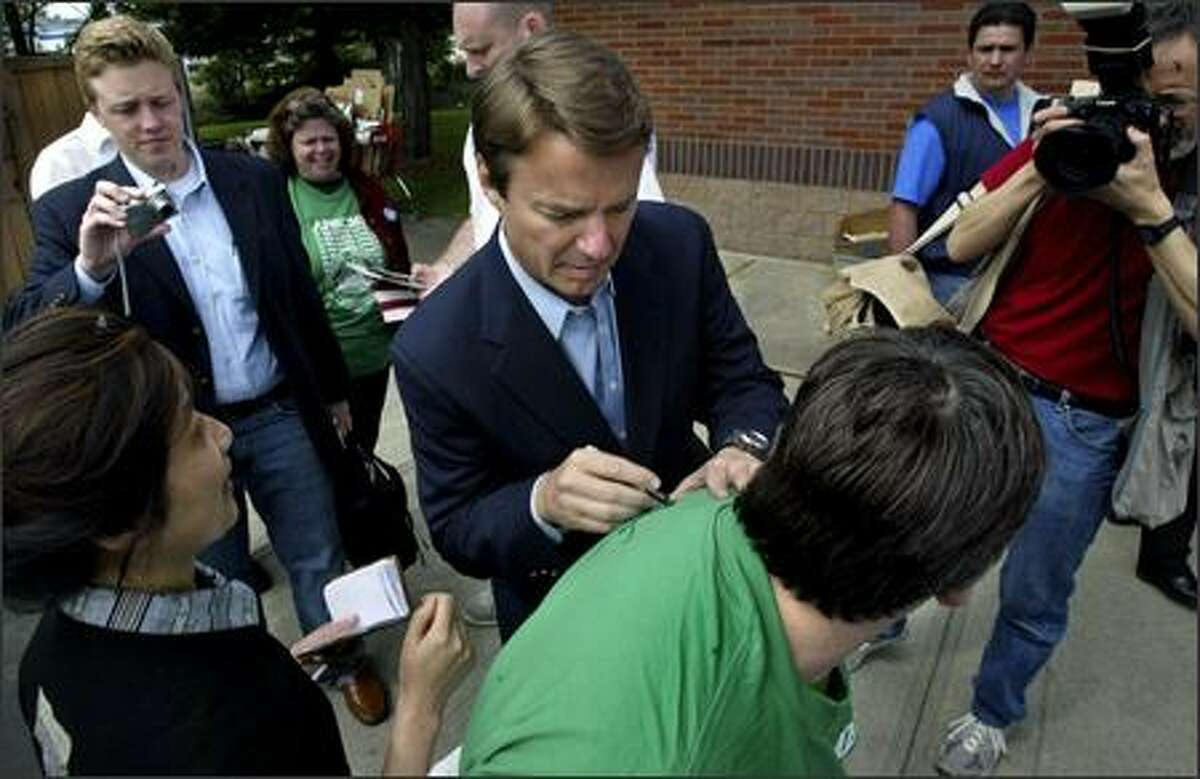 Democratic presidential candidate John Edwards signs the t-shirt of Zach Smith, with the American Federation of State, County and Municipal Employees as he prepares to leave after speaking to union members Tuesday, May 1, 2007 in Seattle.