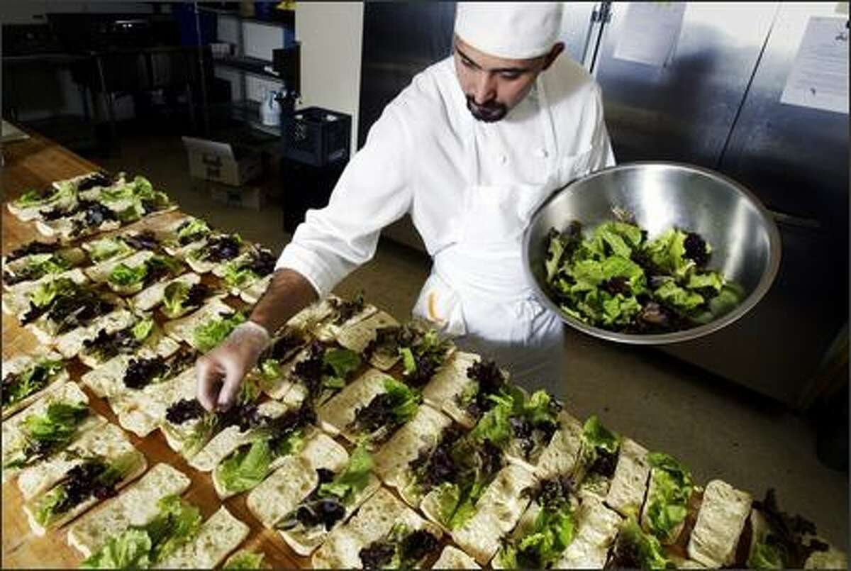 Herban Feast employee Juan Martinez adds baby lettuce from Willie Green's Organic Farm to some of the 220 sandwiches prepared at the catering business Tuesday.