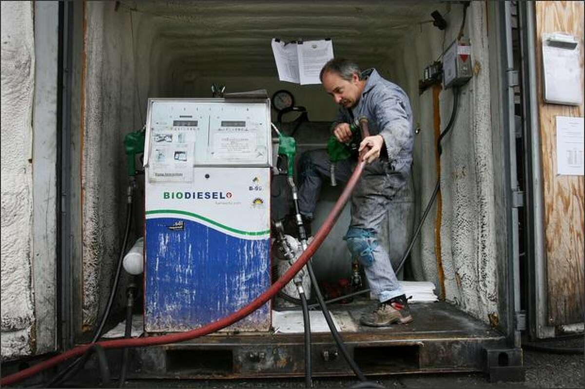 Dan Freeman, owner of Dr. Dan's Alternative Fuelwerks, removes the nozzle after filling the 750-gallon biodiesel dispensing tank at his garage in Seattle's Ballard neighborhood.