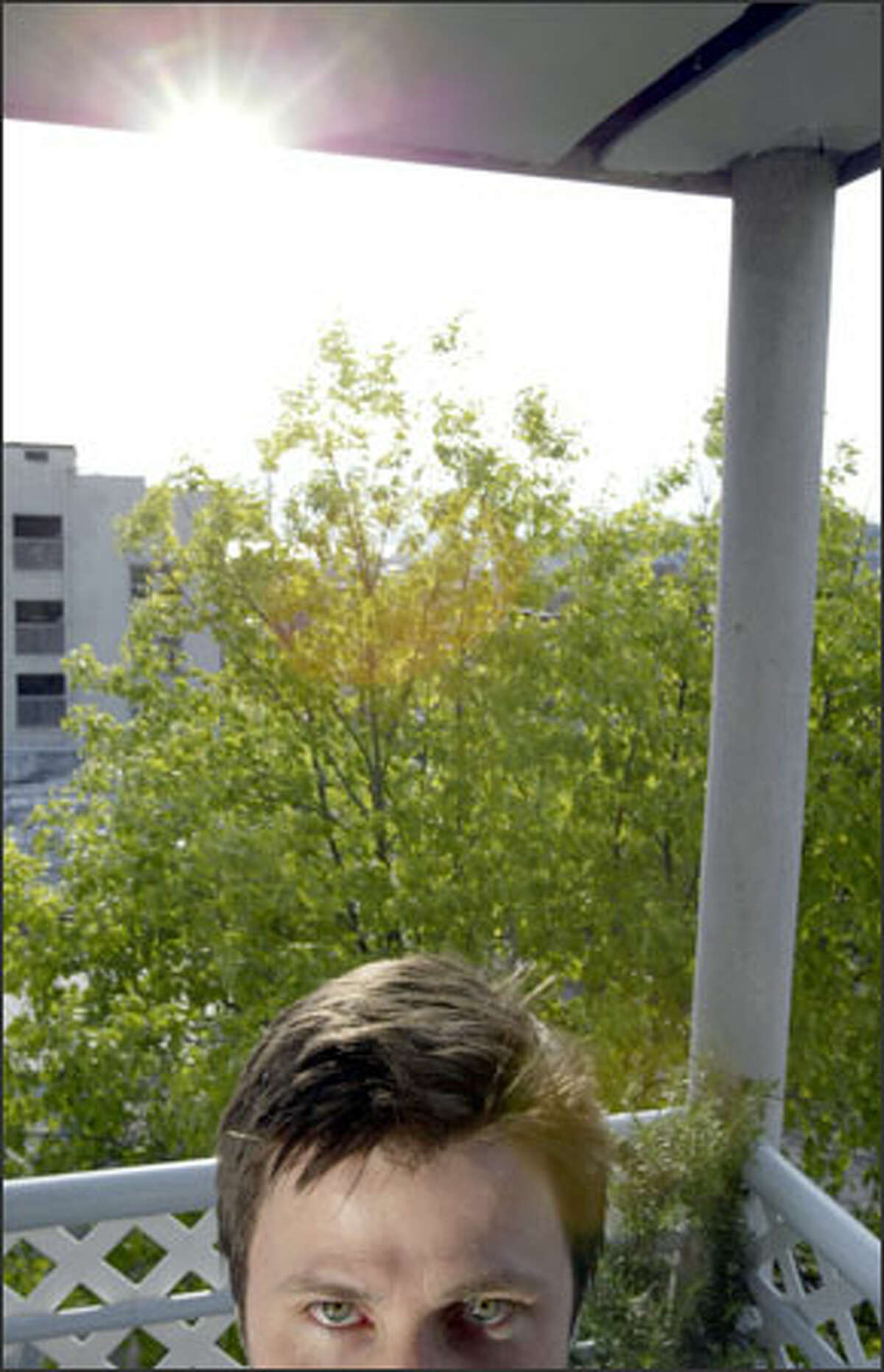 Bryan Lhuillier points out his view-blocking tree from the deck of his apartment on Seattle's Capitol Hill.