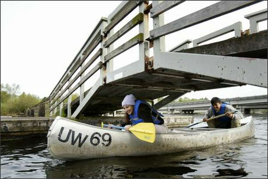 Feriyal Aslam and Wilmar Salim, from Los Angeles, pass under a footbridge connecting Marsh and Foster islands. Photo: Joshua Trujillo, Seattlepi.com / seattlepi.com