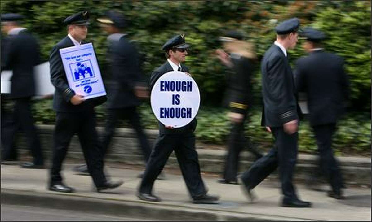 Hundreds of Alaska Airlines pilots picket along International Blvd. in front of Alaska Airlines headquarters in SeaTac and on Tuesday. The nearly 1,500 pilots of Alaska Airlines currently are in contract negotiations.