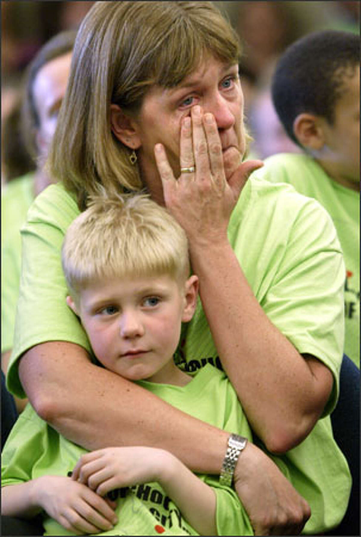 Lynne Butz tears up while holding onto her son, Simon, 7, at a Seattle School Board meeting. More than 200 parents and students turned out to protest the district's plan to close 10 schools.