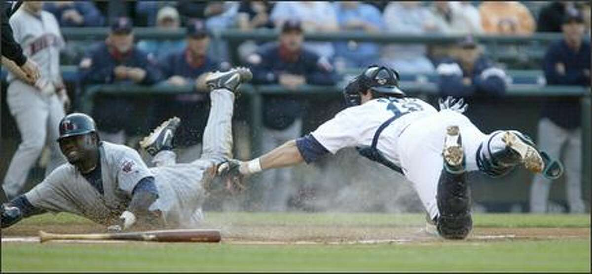 Mariners catcher Ben Davis tags out Minnesota's Cristian Guzman at the plate in the first inning.