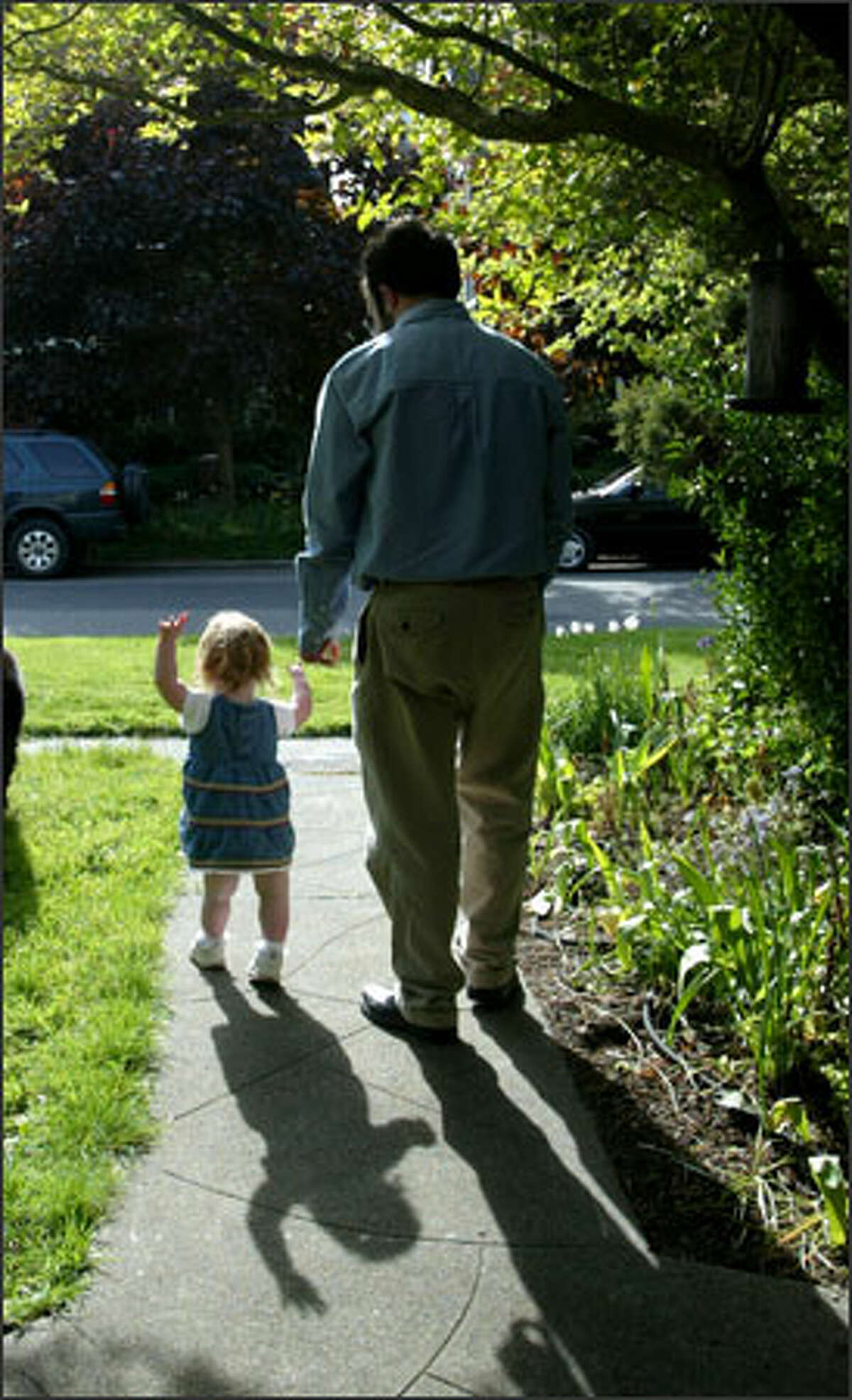Rob Farrow takes a walk with Samantha in front of their home in Seattle. Because Samantha was robbed of key muscle tone, she still lags behind her peers and didn't start walking until she was 26 months old.