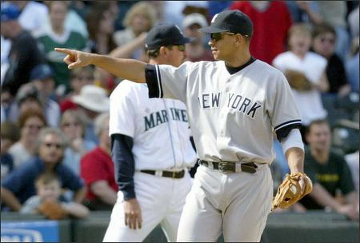 After catching Ichiro Suzuki's line drive to end the game, Alex Rodriguez (2-for-3, HR) points to manager Joe Torre, who had moved the third baseman closer to the line before the play.