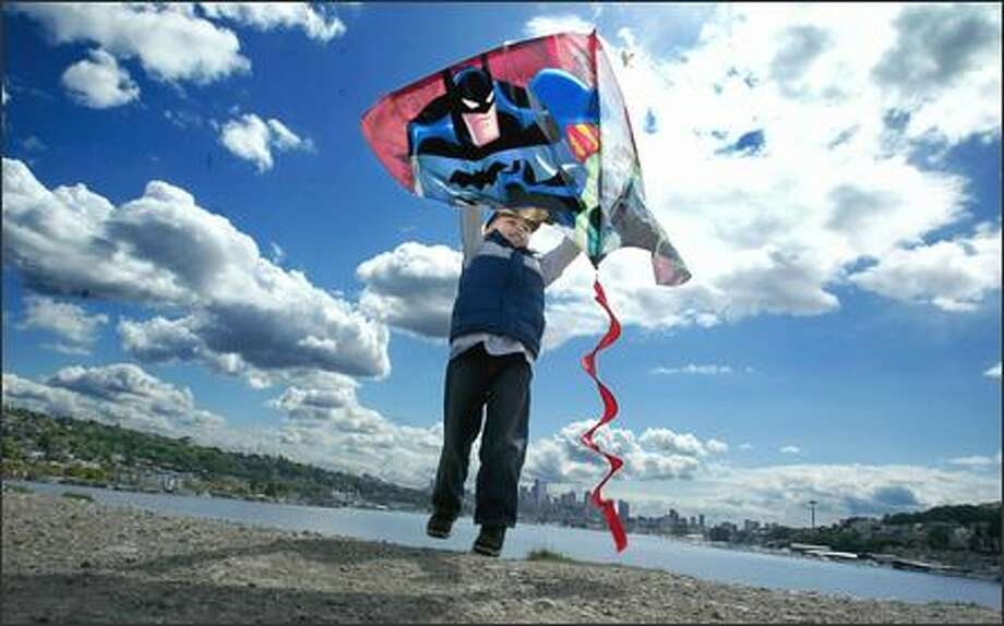 Five-year-old Marcus Figueroa is all smiles as he gives his superheroes a lift as his dad, Louis, pulls the string and the kite takes flight Monday at Gas Works Park. Photo: Scott Eklund, Seattle Post-Intelligencer / Seattle Post-Intelligencer