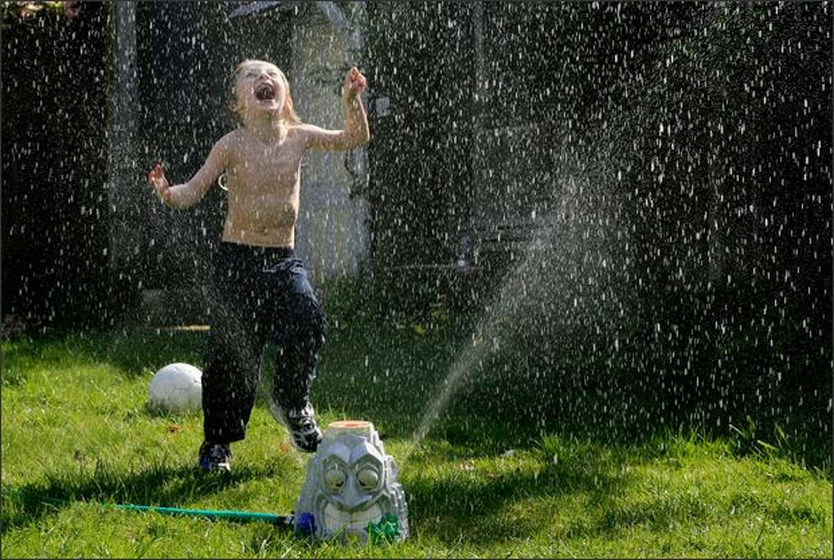 Sharky McGarry, who is autistic, plays in a sprinkler outside his Capitol Hill apartment in Seattle.