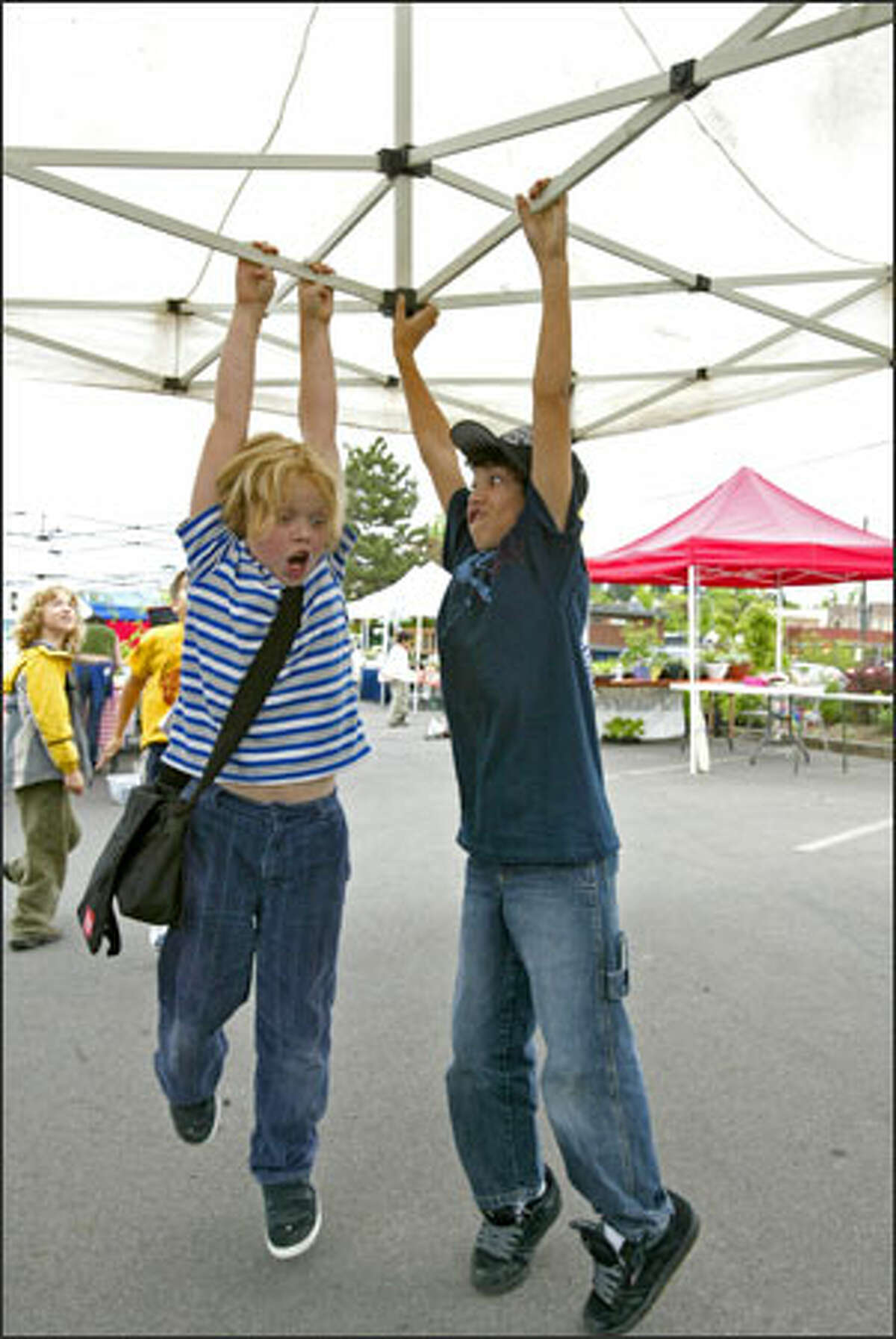 The Columbia City Farmers Market opened for its eighth year with help from Orca at Columbia Elementary School students. Third-graders Lowell Horvitz, left, and Manny Talevich are taken by surprise as they are lifted off the ground while helping raise a pop-up canopy for a vendor's stand.