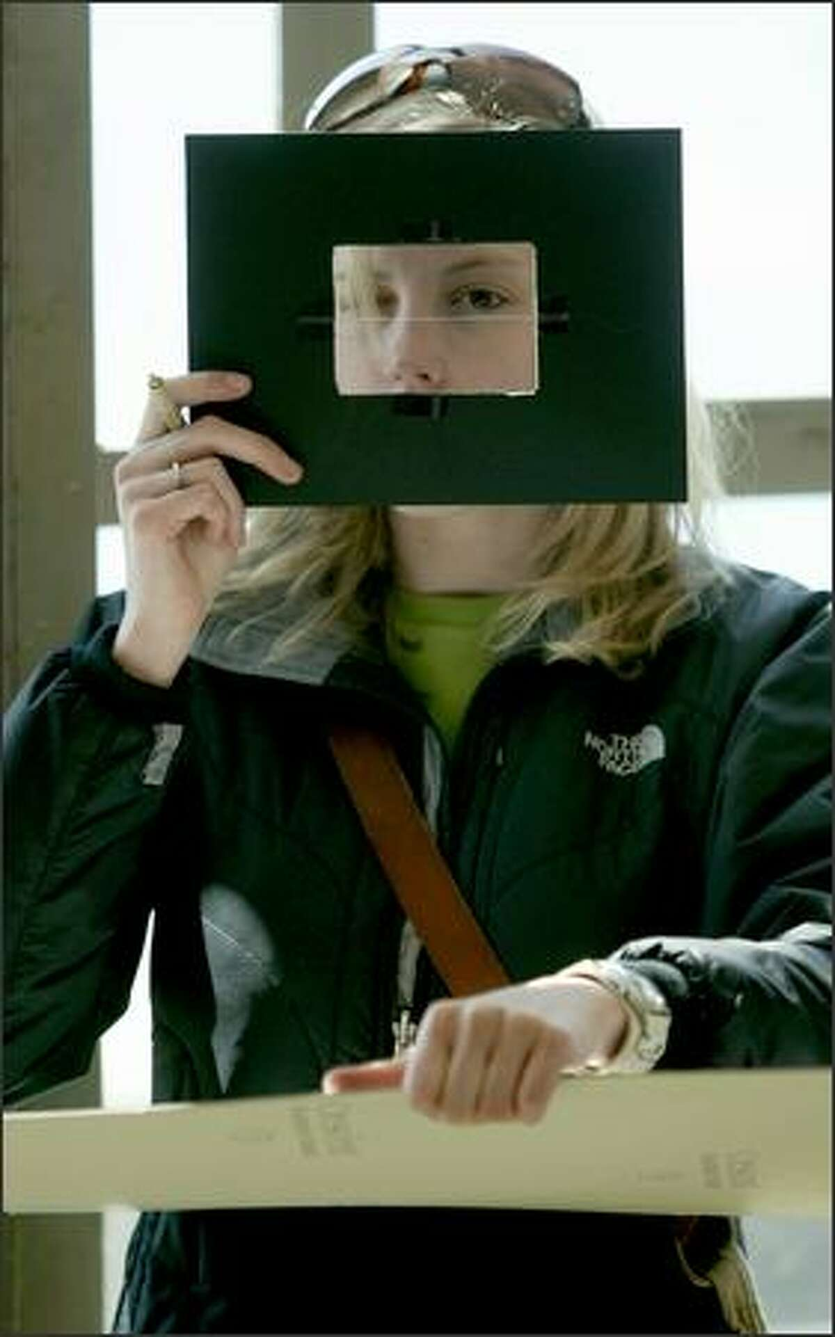 Samantha Nicklay, an architecture student at the University of Washington, peers through a cardboard viewfinder Tuesday as she inks perspective drawings of Pike Place Market in Seattle. The viewfinder aids in composition and helps gauge lines as they converge in perspective.